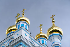 Golden church domes. Contrast golden church domes with crosses on dark grey sky background Stock Images