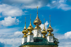 Golden Church domes. Golden Church domes on the background of blue sky with beautiful clouds stock photo