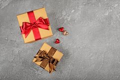 Golden classic shiny gift boxes with satin brown and red bows and small hearts. On gray concrete background Stock Photography