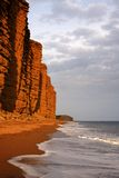 Golden cliffs at West Bay. Late evening sunlight casts a warm golden glow on the faces of the steep cliffs at West bay in Dorset. The calm sea washes onto the Royalty Free Stock Photo