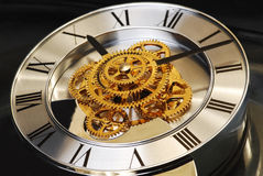 Golden Clock. With gears and latin digits Stock Photos