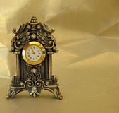 Golden Clock. A vintage clock shot on a golden background Stock Photo