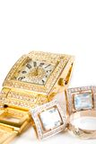 Golden clock and jewellery Stock Images