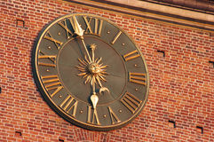 Golden clock in Krakow. Golden clock in red wall of city hall tower in Krakow, Poland Stock Photos