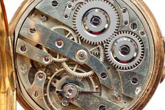 Golden Clockwork on white background. Detail of watch machinery. Old mechanical pocket watch. Macro shot. Royalty Free Stock Photos