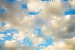 Golden clouds blue sky. Abstract blue sky shot with soft clouds and golden glow Stock Images