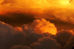 Golden clouds on fire. Beautiful sunset above the clouds from an airplane window Royalty Free Stock Photography