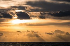 Golden cloudy sunset sky with shadow over dark sea. At Phuket of Thailand Royalty Free Stock Image