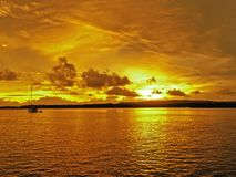 Golden coastal cloudy sunrise seascape. A picturesque inspirational brightly coloured gold and orange cloudy cumulus tropical sunrise seascape with ocean water stock image