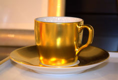 Golden coffee cup Stock Images