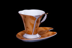 Golden coffee cup with saucer on black background Stock Photos