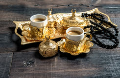 Golden coffee cups rosary beads wooden background Stock Image