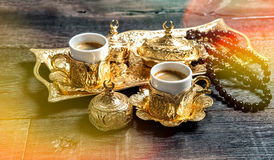 Golden coffee cups rosary beads wooden background light leaks Stock Photography