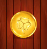 Golden coin with clover on brown wooden texture for St. Patrick Royalty Free Stock Image