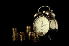 Golden coin stack and vintage clock on dark background Royalty Free Stock Images