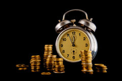 Golden coin stack and vintage clock on dark background Royalty Free Stock Image