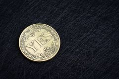 Golden coin with the word Yes on dark black background using as coice or fortune in life or decision in life, gambling or lucky. Coin royalty free stock photography