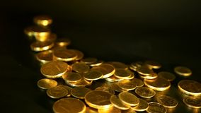 Golden coins on black background. Success of finance business, investment,monetization of ideas, wealth, banking concept. Management efficiency. Golden coins on stock footage