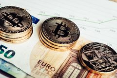 Crypto currency Bitcoin. Golden coins of crypto currency Bitcoin and Euro paper money stock images