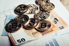 Crypto currency Bitcoin. Golden coins of crypto currency Bitcoin and Euro paper money royalty free stock image