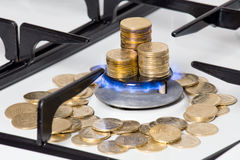 Golden coins on gas cooker Stock Image