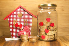 Golden coins in jar and house Stock Images