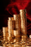 Golden coins in rows. Golden coins on red background Stock Photography