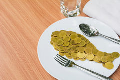 Golden coins shape fish with spoon and fork in white plate stock photos