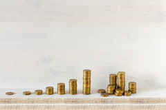 Golden coins stacks arranged as a graph on a wooden background. Business growth and Saving money concept Stock Photo