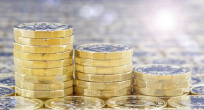 Golden coins in three descending stacks with lights effects. Golden coins with light effects. British pound coins in three descending stacks on a background of stock images