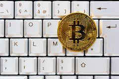 Golden color bitcoin on a computer keyboard Stock Photography