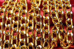 Golden color chain over red silk Stock Photos