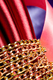Golden color chain over red silk Royalty Free Stock Photo