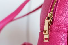 Golden color lock zipper on pink backpack royalty free stock images