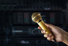 Golden color microphone in woman hand in backstage of concert Royalty Free Stock Photos