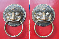 Golden colored chinese door knockers on a red gate Royalty Free Stock Photos