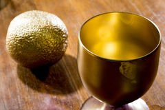 Golden colored close up of a glass and an orange Royalty Free Stock Photo