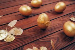 Golden colored Easter eggs with dry flowers over dark wooden planked background.
