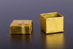 Golden Colored Gift Box on Table. Open, golder colored gift box on wooden table royalty free stock photos