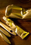 Golden colored tube and crushed can and parts of brushes Stock Images