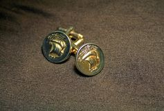 GOLDEN COLOURED CUFF LINKS ON A BROWN BACKGROUND. Image of a pair of decorative golden coloured cuff links  with a sailing ship motif Stock Photo