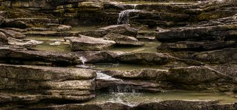Golden rocks with small waterfall. Royalty Free Stock Image