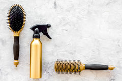 Golden combs and spray for hairdresser work on stone desk background top view mock-up Stock Image