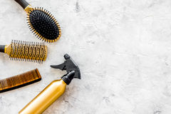 Golden combs and spray for hairdresser work on stone desk background top view mock-up Royalty Free Stock Photos