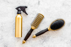 Golden combs and spray for hairdresser work on stone desk background top view Royalty Free Stock Photography