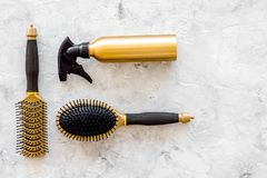 Golden combs and spray for hairdresser work on stone desk background top view mock-up Stock Photography
