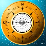 The Golden Compass. A gold compass on a blue background Royalty Free Stock Photography