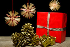 Golden cones, gifts and straw stars on wooden table Stock Photography