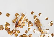 Golden confetti in champagne glasses on the white background. royalty free stock images
