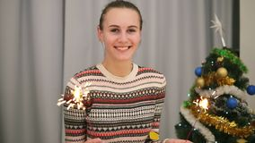 Golden confetti falling on young smiling woman with the Christmas tree and garlands on the background holding sparklers. And looking to the camera. Slowmotion stock footage